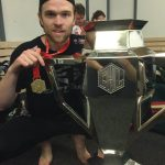 Spencer Abbott wearing a Medal crouching beside a CHL trophy.