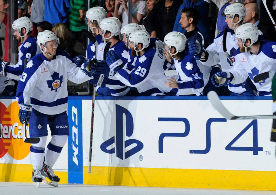 Spencer Abbott receiving high fives from the rest of the Toronto Maple Leafs team.